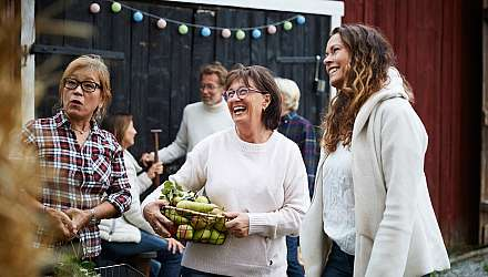 Three women laughing together at a market in Scandinavia