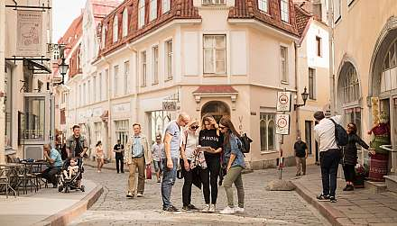Group of four friends looking at iPad in streets of Tallinn