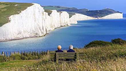 Two people sat on beach looking at white cliffs
